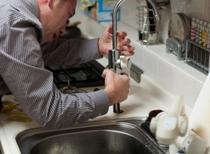 A plumber fixing the sink, the best way to avoid dangers of DIY plumbing projects.