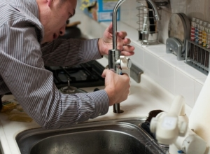 A plumber fixing a low-pressure faucet, one of the hidden signs that something is not right with your plumbing.